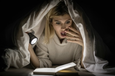reading book under bed cover and holding a flashlight
